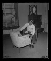 Ice Cream salesman Mark Marlatt, with chair purchased at Hollywood Hotel closing auction, 1956.