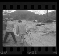 Boat with children is pulled across flooded Topanga Creek by a cable, Topanga, 1969