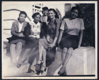 Unidentified African American women posing on a wall, Los Angeles, 1940s