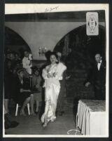 L'Tanya models a white satin dress, Los Angeles, 1940s