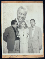 """James """"Buddy"""" Garcia and Alyce Key in front of a poster of Louis Armstrong, Los Angeles, 1940s"""