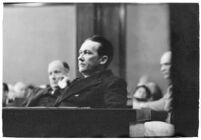 Widower Robert S. James sitting in a courtroom during an inquest involving his wife's death, Los Angeles, 1935