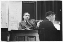 Murder suspect Robert S. James sitting on the witness stand with a plan of his house behind him, Los Angeles, 1936