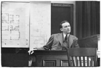 Murder suspect Robert S. James sitting on the witness stand with a map of his house behind him, Los Angeles, 1936