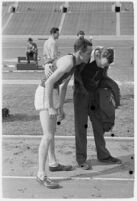 USC track athlete speaking to a coach on the Coliseum field, Los Angeles, 1937