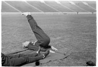 USC track athlete stretching on the field at the Coliseum, Los Angeles, 1937