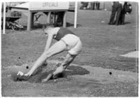 USC track athlete landing in sand after a jump, Los Angeles, 1937