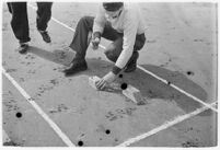 Sports official making marks on the track at a meet between UCLA and USC, Los Angeles, 1937