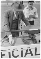 Sports official using a scale at a track meet between UCLA and USC, Los Angeles, 1937