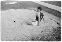 Track athlete landing in sand after a jump at a track meet between UCLA and USC, Los Angeles, 1937
