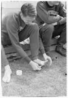 USC track athlete taping his foot on the sidelines at a meet, Los Angeles, 1937