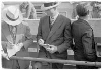 Sports officials writing down times at a track meet between UCLA and USC, Los Angeles, 1937
