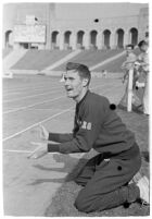 USC track athlete clapping on the sidelines at a meet, Los Angeles, 1937