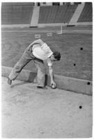 Sports official retrieving the shot at a track meet between UCLA and USC, Los Angeles, 1937