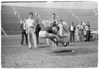 Track athlete completing a jump at a meet between UCLA and USC, Los Angeles, 1937