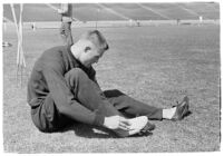 USC track athlete taping his foot on the field, Los Angeles, 1937
