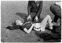 Sports officials examining a USC track athlete for injury, Los Angeles, 1937