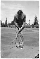 LA Daily News city editor Charles Judson demonstrates improper golf swings for a tutorial series with golfer Fay Coleman.  Circa 1940.