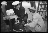 Porter helping a passenger with her luggage outside of the S.S. Mariposa, Los Angeles