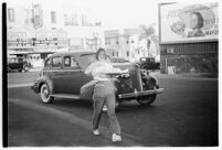 Drive-in waitress carrying a meal to a customer, Los Angeles, 1937