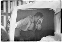 Unidentified man in an ambulance after being injured during a workers' strike, Los Angeles, 1937