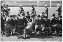 Loyola Lions in a huddle with their coaches on the Coliseum field, Los Angeles, 1937