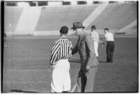 Football coach speaking to a referee on the Coliseum field, Los Angeles, 1937
