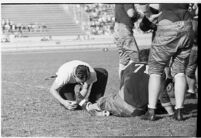 Football player having his foot taped during a game between the Loyola Marymount Lions and St. Mary's Gaels at the Coliseum, Los Angeles, 1937