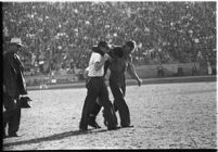 Injured Loyola Lions football player being helped across the field at the Coliseum, Los Angeles, 1937