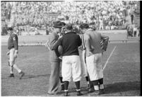 College football coach Buck Shaw confers with referees during a game, October 24, 1937.
