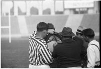 Loyola Lions' coach Tom Lieb and referees with player, during game against Santa Clara's Broncos at the Coliseum, Los Angeles,  1937