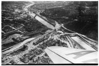 Aerial view of rushing flood waters moving down the Los Angeles River in North Hollywood, Los Angeles, 1938