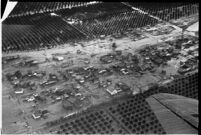 Aerial view of rushing flood waters destroying homes and crops in North Hollywood, Los Angeles, 1938