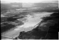 Aerial view of flood water moving down a river and destroying crops in North Hollywood after a major flood, Los Angeles, 1938