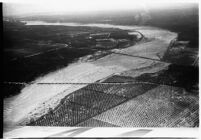 Aerial view of rushing flood waters moving down a river in North Hollywood, Los Angeles, 1938