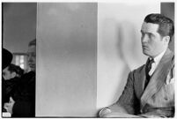 Thomas W. Warner, Jr. sits next to private detective Pearl Antibus who was suing his millionaire father for damages that resulted from a raid on her home, Los Angeles, 1938