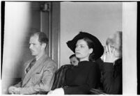 Private detective Pearl Antibus shields her face as she appears in court with her daughter Norma Thelan during her trial against millionaire Thomas W. Warner, Sr, Los Angeles, 1938