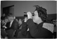 Female spectator uses binoculars to view court proceedings during the trial of Police Captain Earle E. Kynette, Los Angeles, 1938