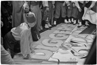 Member of the Mystic Shrine attending to a sign for the Durbar festival, Los Angeles, 1937