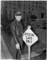 "Deputy Sheriff George R. Burns standing next to a sign that says ""Official Cars Only,"" Los Angeles"