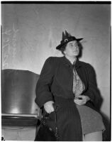 Veronica Greuzard wearing an overcoat and sitting in a chair, Los Angeles, 1937