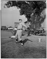 Bob Winslow, pitcher for the USC Trojans baseball team, warming up his arm on the sidelines, Los Angeles, 1940