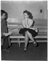 Merle McClurg sitting on a bench talking to an unidentified man, Los Angeles