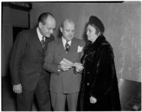 Attorney R. M.  Trezevant reading a piece of paper with Carl and Ruby Crockett, Los Angeles