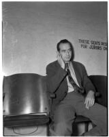 Bill Thompson smoking a cigarette while seated in a chair reserved for jurors only, Los Angeles