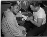 Boxer Henry Armstrong getting his hand wrapped in tape, Los Angeles, 1930s