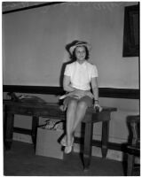 Mrs. Inez I. Allen seated on the edge of a table wearing a hat, Los Angeles