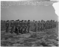 """Soldiers in old military uniforms stand next to others wearing the new """"streamlined"""" style during a military show for National Defense Week, Los Angeles, 1940"""