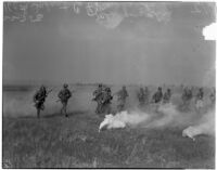 Soliders of the 160th Infantry charge through a smoke screen during a military show for National Defense Week, Los Angeles, 1940