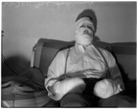 Joe Schrank sits on a couch with his hands and face completely wrapped in bandages, Los Angeles
